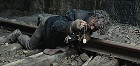 A man with dirty and tousled hair is seen lying on his stomach on a train track, examining a watch that he is holding with his right hand. His shirt is dirty with mud on it and his gloves are torn, baring his fingers. His shoes are also muddy.