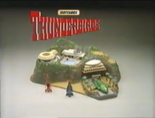 "Scale, toy model of a tropical island, with stationary, futuristic air- and spacecraft and ""Thunderbirds"" title"