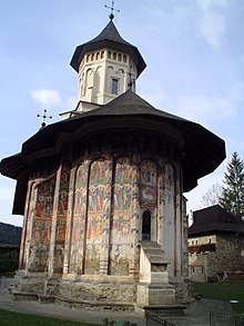 A small chapel in the grounds of a monastery has the walls decorated with four tiers of frescos in rich colours, faded and damaged by the weather. The roof of the chapel overhangs the walls to protect the murals.