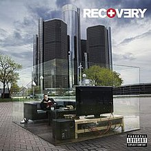 The cover image features skyscrapers in center under cloudy blue sky. Above which, on the ground, transparent glass-type cuboidal body is placed. Inside which, appears a living room with Eminem seated on sofa watching television. On top-left corner, in bold and capitalised format, the title RECOVERY appears.