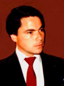 A young man wearing a suit and a red tie