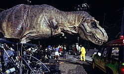 A life-sized Tyrannosaurus robotic model, with hydraulics  where the dinosaur's feet would be, touches a car in a movie set.