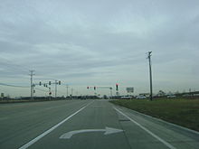 Approaching intersection with IL 60. Road is 2 lanes in each direction, concrete lanes. Traffic signal lies ahead from viewpoint of right turn lane.