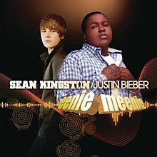 "Two young men are looking forward. The man of the left is wearing a green jacket and has his hands on his pockets. Moreover, the man of the right is wearing a plaid blue shirt, and has his hands on his chest, the background is black and in front of them the words ""Sean Kingston / Justin Bieber"" are written in flesh capital letters, while ""Eeenie Meenie"" are in lower case letters."