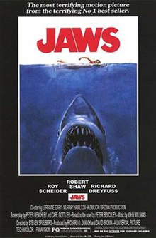 "Movie poster shows a woman in the ocean swimming to the right. Below her is a large shark, and only its head and open mouth with teeth can be seen. Within the image is the film's title and above it in a surrounding black background is the phrase ""The terrifying motion picture from the terrifying No. 1 best seller."" The bottom of the image details the starring actor and lists credits and the MPAA rating."