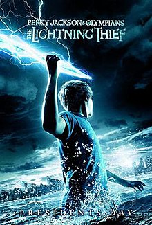 A youth, standing in a large body of water in the dark, holds a bolt of lightning in his raised right arm and faces away, towards a city skyline