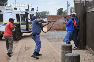 South African general election, 2014 - ICASA ordered that this photograph of a police officer firing rubber bullets at unarmed residents during a protest in Bekkersdal over an ANC election campaign be removed from a DA election campaign television advert.