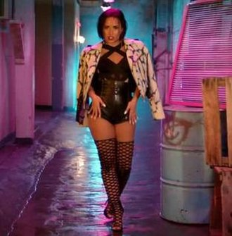 """Cool for the Summer - A screenshot from the music video, showing Lovato wearing black latex and boots. In a scenery which Joe Lynch from Billboard described as a """"neon-drenched ode to summer fun—with an emphasis on what happens after dark""""."""