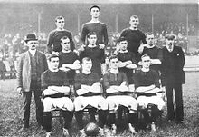 A black-and-white photo of a football team. The players are on three levels, with four on the bottom row, four on the middle row and three on the top row. The player sitting second from the left on the bottom row has a ball at his feet, and the player in the middle of the top row is wearing a flat cap.