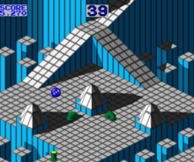 Horizontal rectangular video game screenshot of the arcade version that is a digital representation of a gridded plane with ramps and spikes. A blue marble is near the center of the screen, with moving green tubes below it.