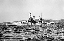 A large light gray battleship tilts back in choppy water as it slowly sinks.