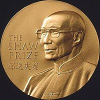 "A gold circular medal with a depiction of an elderly man with glasses wearing a jacket buttoned to the neck; the English words ""The Shaw Prize"" and Chinese characters ""邵逸夫獎"" engraved on it"