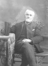 Photo of William Bickerton sitting in a chair.