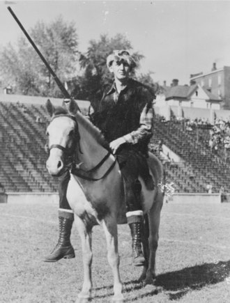"West Virginia Mountaineer - Boyd ""Slim"" Arnold, the first Mountaineer mascot to don the traditional buckskin uniform. His selection in 1937 marked the beginning of an official process to appoint the mascot annually."