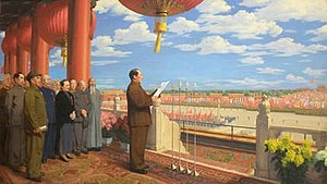 Mao stands on a balcony overlooking Tiananmen Square. He reads a speech with other leaders gathered behind him.