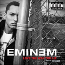 A monochrome still of Eminem, leaning on a perimeter fence to the right.