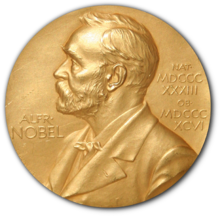 "A golden medallion with an embossed image of a bearded man facing left in profile. To the left of the man is the text ""ALFRo"" then ""NOBEL"", and on the right, the text (smaller) ""NATo"" then ""MDCCCXXXIII"" above, followed by (smaller) ""OBo"" then ""MDCCCXCVI"" below."