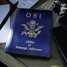 "A blue book similar to an American passport lies on a desk surrounded by papers, folders, a pen and a glass of water. The blue book has ""OSI"" printed on its top centre, and ""Office of Strategic Influence"" along the bottom centre of the book in smaller text. The eagle found on American passports has been altered: the arrows are double-headed, the olive branch is wilted, and the eagle's wings have been clipped."