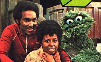 The Robinson family (Sesame Street) - Miller as Gordon, with Long as Susan and Caroll Spinney as Oscar the Grouch. Undated publicity photo, likely from 1972.