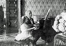 a young girl and an elderly man duetting at a grand piano