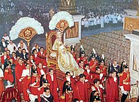 Pope Pius XII, in coronation robes and wearing the 1877 Papal Tiara, is carried through St Peter's Basilica on a sedia gestatoria. Image courtesy of Wikipedia.