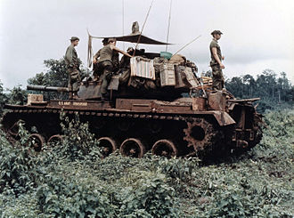 M48 Patton - Men of Troop B, 1st Squadron, 10th Cavalry Regiment, 4th Infantry Division, and their M48 Patton tank move through the dense jungle in the Central Highlands of Vietnam in June 1969.