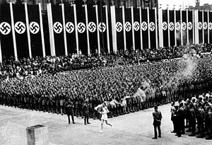 Olympic flame - At the end of the first Olympic torch relay, the Olympic flame arrives in Berlin, 1936