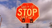 "In the photo, a red stop sign can be seen. On the stop sing, the word ""Stop"" is in the center, and written above it are the words ""This Is it"" and at the bottom of the sign, the word ""Hatin'"" is written in capital letters; all the words on the sign are written in yellow. In the background, a blue sky, that is mainly full of white clouds, is shown and a metal poll is shown behind the sign."