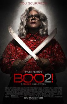 a madea halloween an elderly black woman looking serious and holding two large blades across her chest above