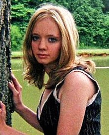 A Caucasian woman with blonde shoulder-length hair wearing a blue tank top with white trim looks to her left directly at the camera with her hands placed on a tree at the left of the image. Behind her is a body of water and some woods.