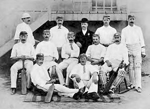 A cricket team arranged in three rows. Apart from one man in a suit, they are all wearing cricket whites.