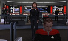 A computer-rendered version of the bridge featured in Star Trek: Voyager. A woman gives orders from the center of the room, while a man works on a console in the foreground. The ship's executive officer sits in a chair to the right, and a crewman works on a panel with the ship's schematics in the background. To the left, a man in an armored uniform watches the activity.