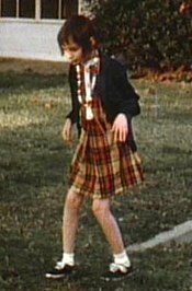 A slightly grainy color picture of Genie, facing slightly right of the camera, walking by herself outside in the Children's Hospital recreation yard. She is wearing a plaid-patterned dress and thin sweater and looks extremely pale, emaciated, and expressionless. Her limbs are exposed and look extremely thin. Both of her knees are very bent, and her arms are bent forward with both hands hanging down as she holds them out in front of her.