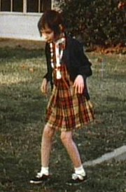 A slightly blurry color picture of Genie, facing slightly right of the camera, walking by herself outside in the Children's Hospital recreation yard. She is wearing a plaid-patterned dress and thin sweater and looks extremely pale, emaciated, and expressionless. Her limbs are exposed and look extremely thin. Both of her knees are very bent, and her arms are bent forward with both hands hanging down as she holds them out in front of her.