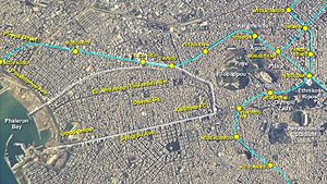 Kallithea - Astronaut photo showing the city of Kallithea (bordered with white dotted line), its location next to the Athens centre (to the right) and the Phaleron Bay (to the left), as well as the local layout of the metropolitan urban railway (cyan line) and its stations (yellow circles). Click box right to enlarge
