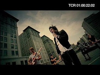 It's Not the End of the World, But I Can See It from Here - A shot of Ian Watkins (right) and Lee Gaze (left) with the rest of the band (background) in a city car park.