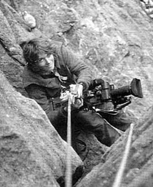 Beverly Johnson (climber) - Johnson with a video camera, roped to a rockface (Mike Hoover)