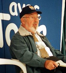 A man wearing a beige jacket while sitting.