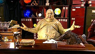 Love & Monsters - An overweight green alien with the face of a human protruding from its belly.