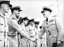 Two men in light-coloured military uniforms with peaked caps, shaking hands in front of a row of similarly dressed men