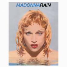 A close-up image of Madonna submerged with her head above water and her hands over her breasts.