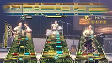 "A video game screen shot that shows three ""note tracks"" along the bottom half and a horizontal bar like a musical staff for the vocalist, overlaid against other interface elements such as a scoring meter, star tracking, and performance meter, and images of the virtual Beatles avatars playing at the specific venue"
