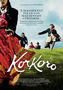 DVD cover for the movie, with a lady in Roma attire in the foreground, her face partially outside the frame, we can see her lips, chin and nose. In the background can be seen three men: one with grey hair, one with long black hair and the last with a hat on. The man with grey hair is shown about to jump. There is also a woman in the background, with not much of her in focus, except that she is wearing purple ethnic clothing.