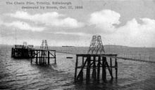 An old black-and-white photograph of a suspension pier. On the furthest platform of the pier are two buildings. There are two steamships in the background. In the foreground a rectangular object floats in the sea.