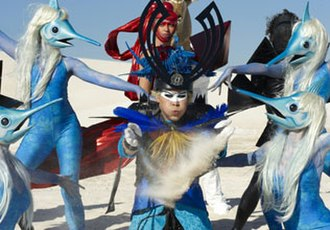 "Standing on the Shore - Luke Steele posing with the swordfish girls and the triangular people whilst blowing some sand across in the music video for ""Standing on the Shore""."