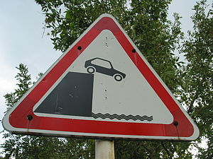 Car off cliff sign