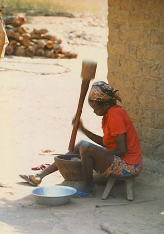 Cassava-based dishes - Woman pounding the cassava root into fufu in the Central African Republic