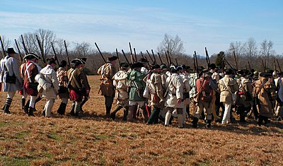 Reenactors portraying Colonial troops march into battle at Cowpens
