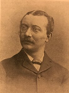 A sepia portrait photograph of a Victorian man wearing glasses, who has a moustache, and is wearing Victorian clothing, looking slightly off centre