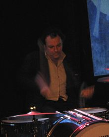 A 45-year-old man is shown at his drum kit. Both drum sticks are blurred in motion. Part of the drum kit is out of view. The man is dressed in a dark jacket with a light shirt, his eyes are focussed down. Behind him is a mostly dark background, past his left shoulder is a blue and white picture.